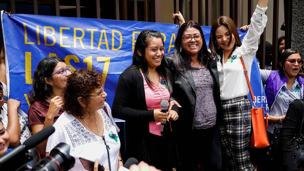 Fem kvinnor står på en liten scen. I mitten är nu frikända Evelyn Hernandez klädd i svar och rosa, med en mikrofon i handen.