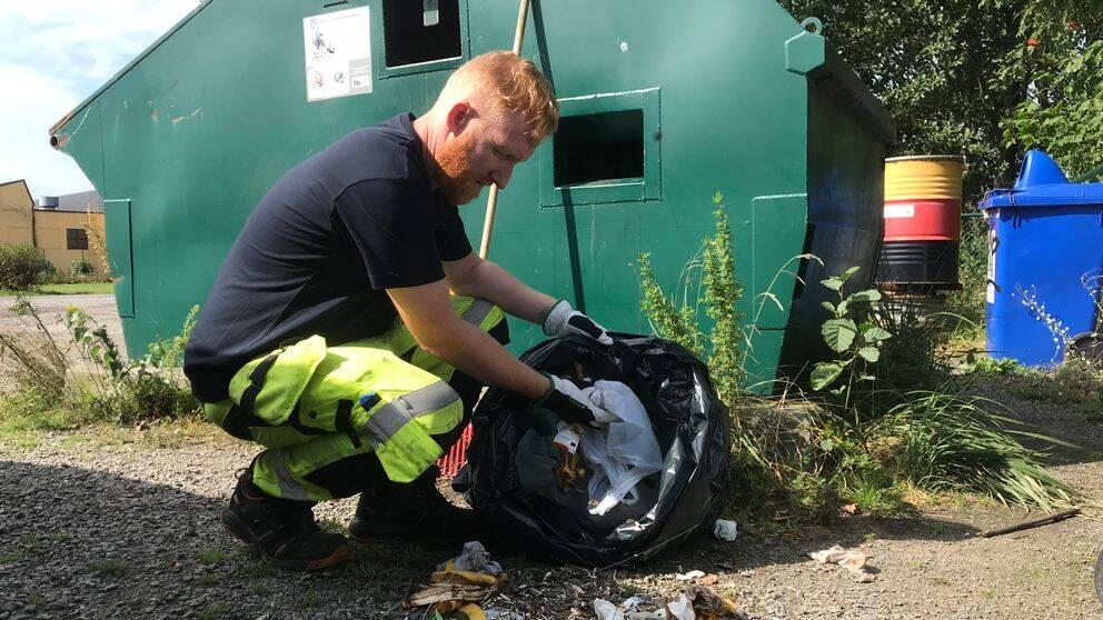 Miljöarbetaren Peter Callander städar upp på en återvinningsstation i Falkenberg.
