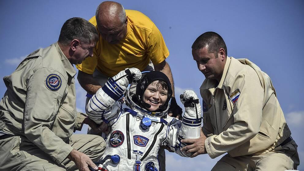 Anne McClain hjälps efter att ha återvänt från sin vistelse på ISS.