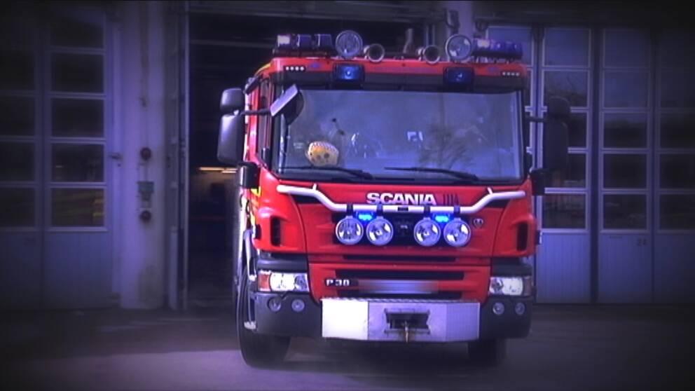 Brandbil på väg ut ur ett garage.