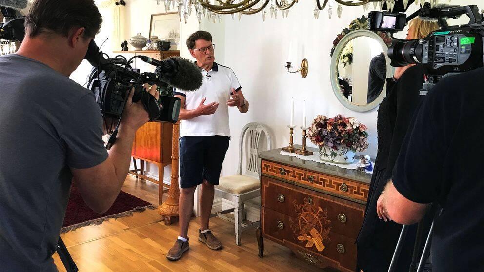Kamerateam filmar en man brevid en antik byrå.