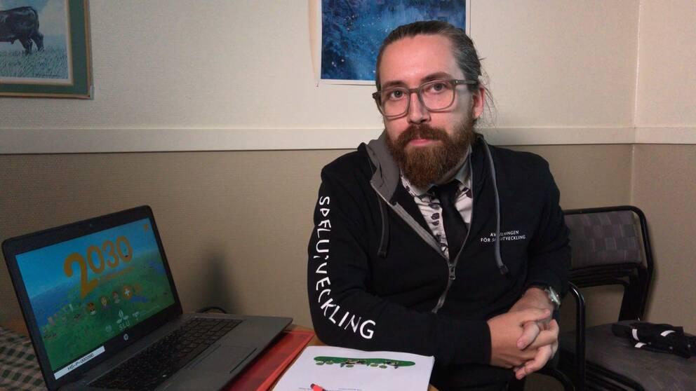 Björn Berg Marklund, spelforskare på Högskolan i Skövde tillsammans med dator där man ser startbilden på spelet KliMat 2030