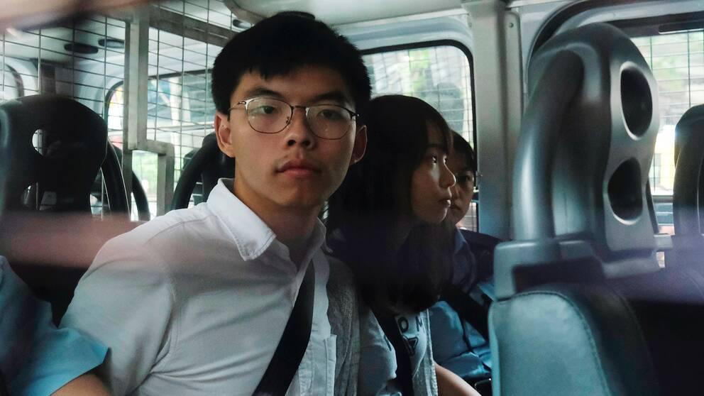 Aktivisterna Joshua Wong och Agnes Chow i en polisbil efter gripandet.
