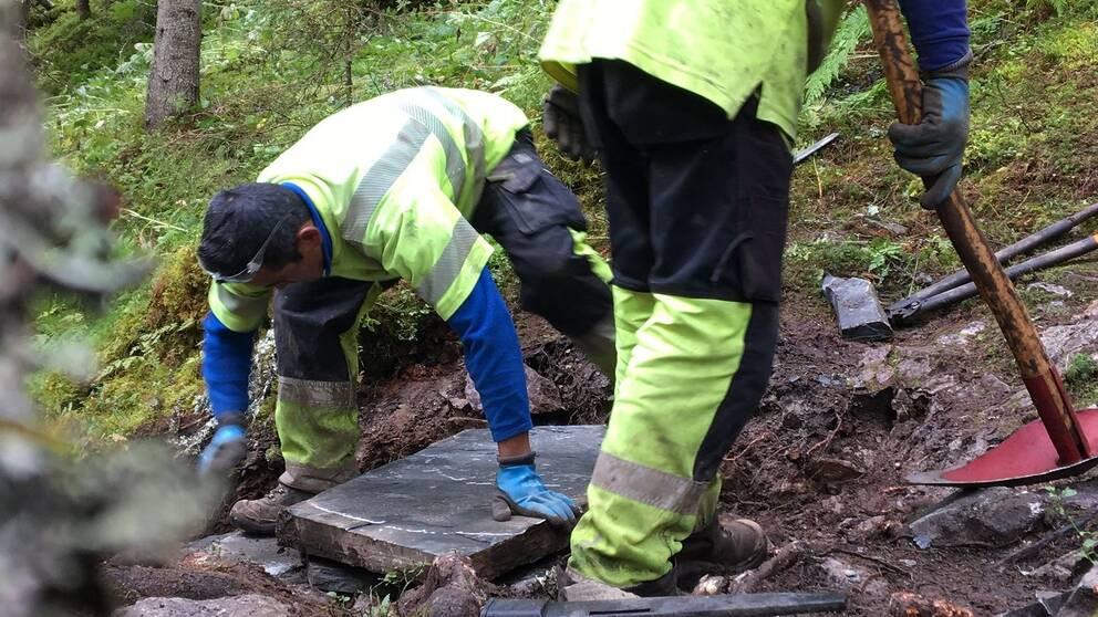 Två sherpas i varselkläder arbetar med att lägga sten på leden upp till Fettjeåfallet