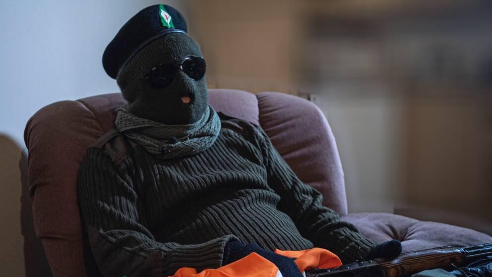En maskerad man från terrorgruppen CIRA sitter i en fåtölj med ett vapen i famnen.