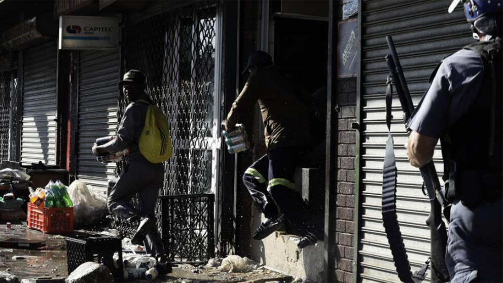 Plundrare som lyckas få med sig varor från en butik i Germiston öster om Johannesburg samtidigt som den sydafrikanska polisen närmar sig.