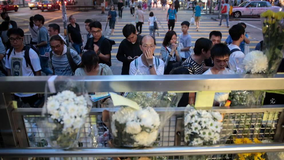 Människor vid ett tillfälligt monument som skapats för de som skadats i protesterna i Hongkong den senaste tiden.