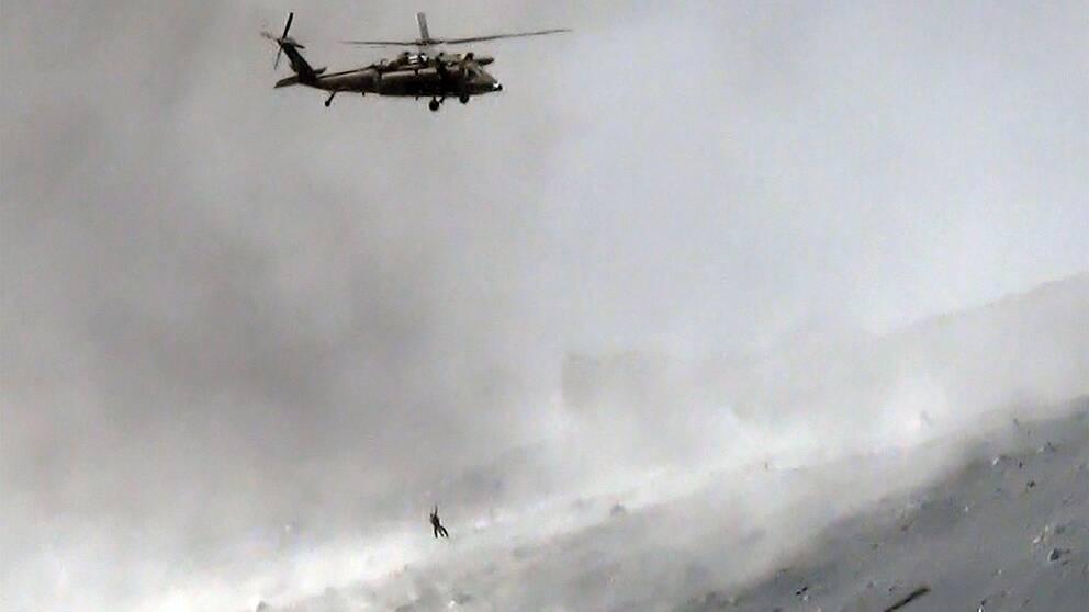 En helikopter från de japanska självförsvarsstyrkorna hämtar en överlevande från vulkanen Ontake.