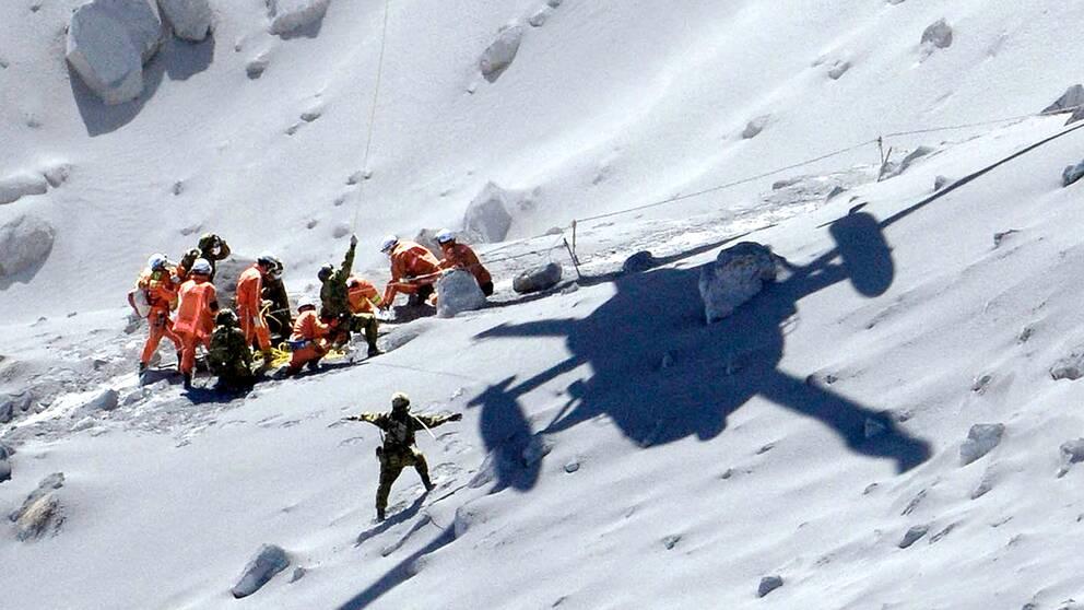 En skadad person hämtas med helikopter. Över 500 personer deltar i räddningsaktionen på vulkanen Ontake.