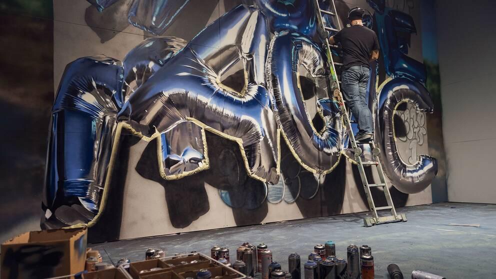Konstnären Huge färdigställer sitt verk inför öppningen av street art-utställningen