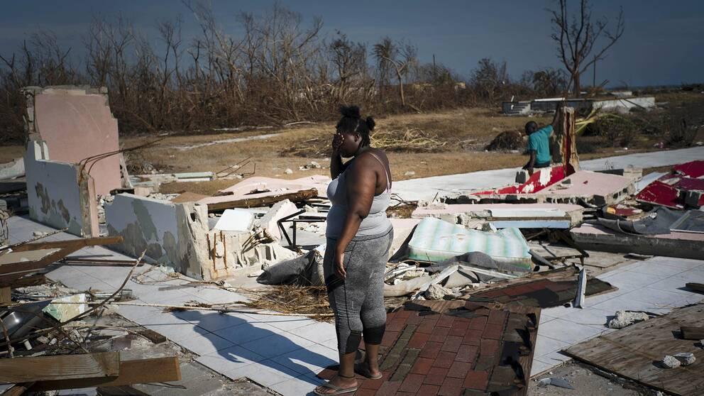 En kvinna tittar ut över sin söndertrasade fastighet i High Rock på ön Grand Bahama.