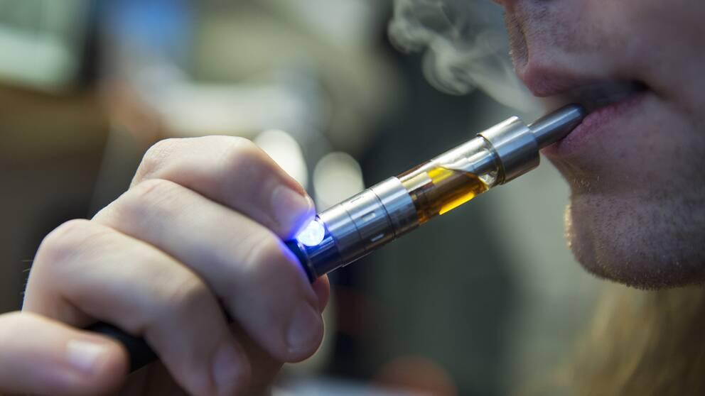 En man röker en e-cigarett