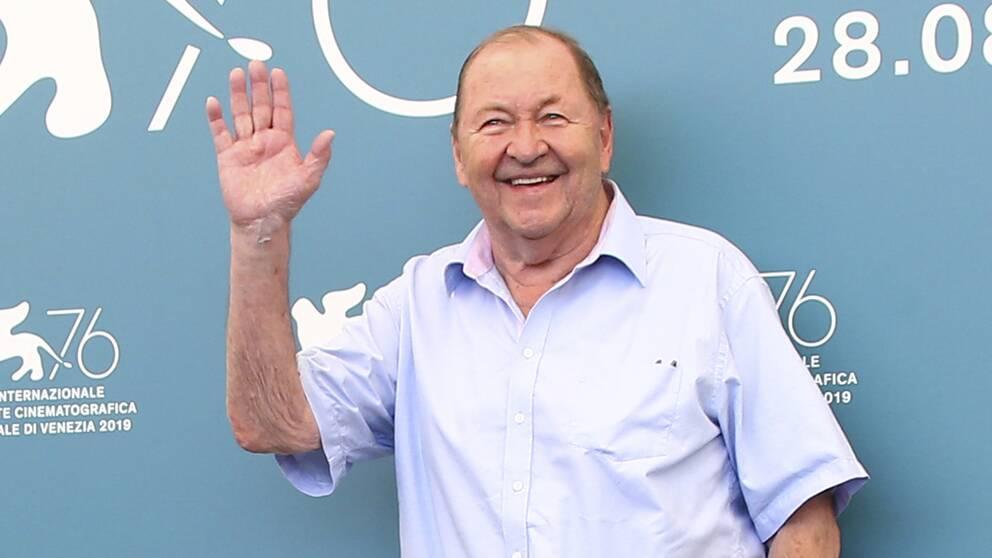 Roy Andersson framför blå fotovägg.