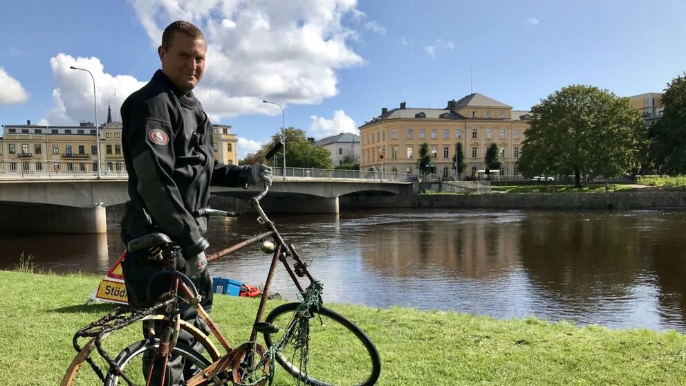 Krisofer Johannesson i Karlstads Dykarklubb står med en cykel som plockats upp ur Klarälven