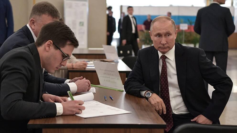 Ryske presidenten Vladimir Putin sitter vid ett skrivbord och väntar på att valförrättare ska registrera honom.