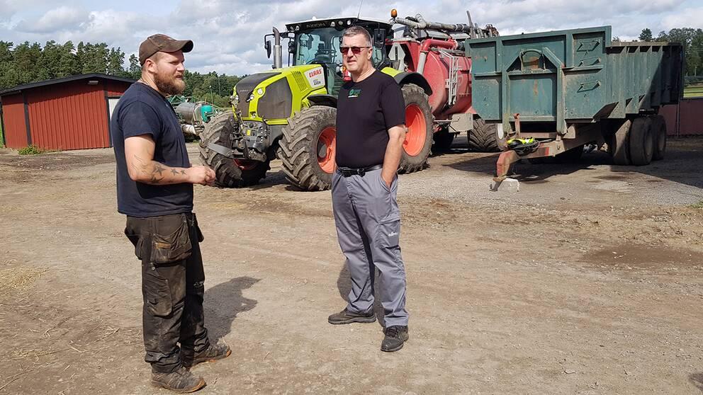 Två män som står på en ladugårdplan framför traktorer.