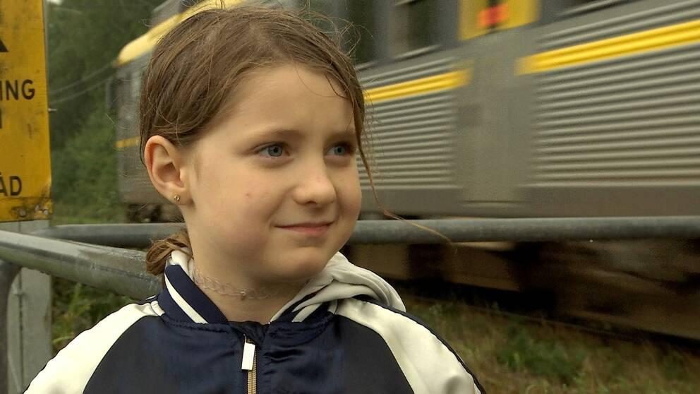 Åttaårig flicka vid järnvägsövergång. Ett tåg passerar bakom henne.