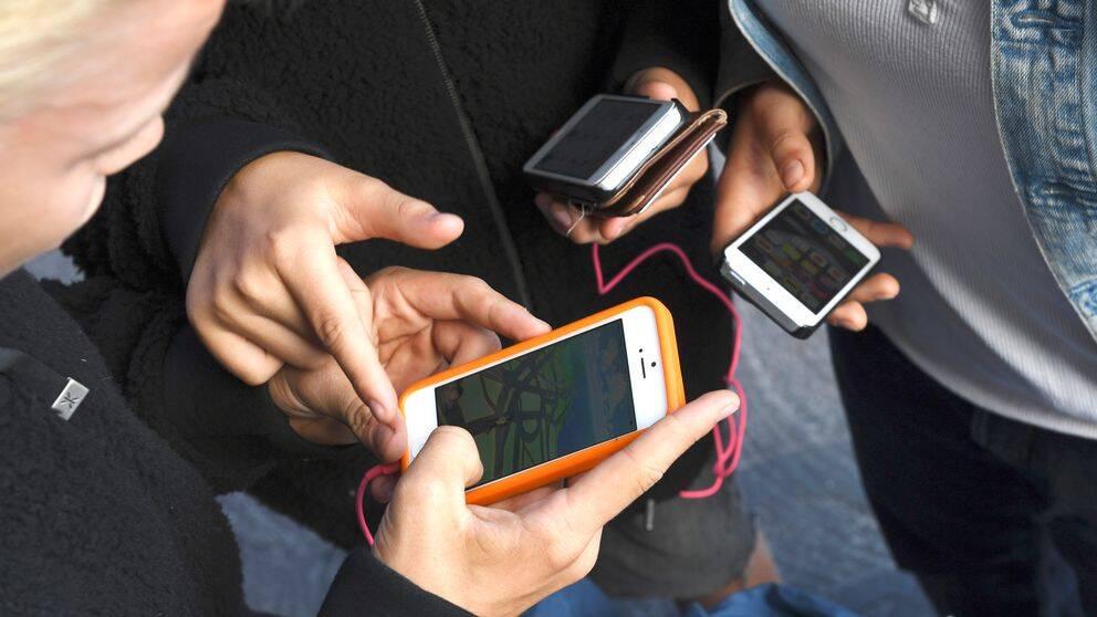 Tre personer kollar sina mobiler. Närbild händer