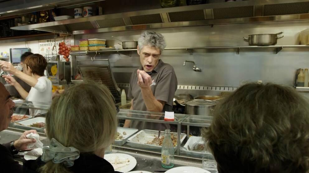 barägaren, Jord Asín, pratar med folk vid bardisk med tapas.