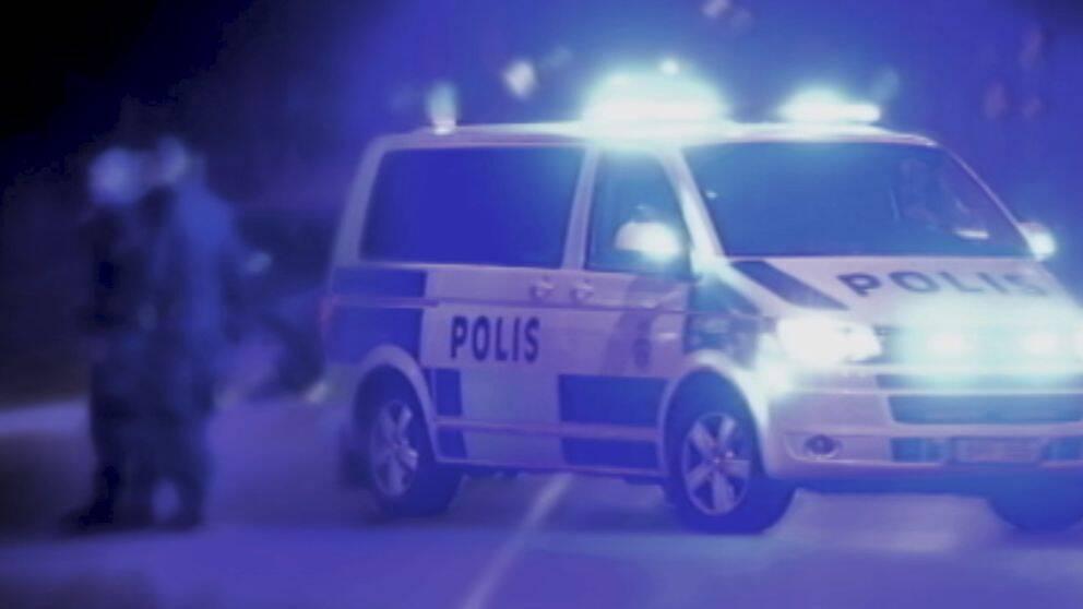 polisens piket-bil på gatan med blåljus på, suddiga figurer