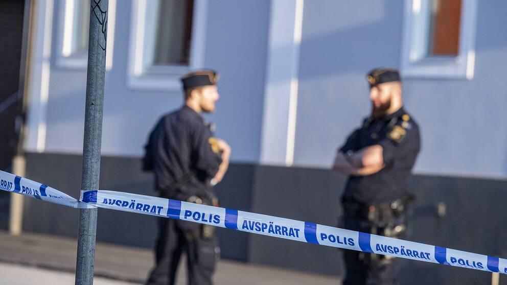 Två poliser bakom en avspärrning.
