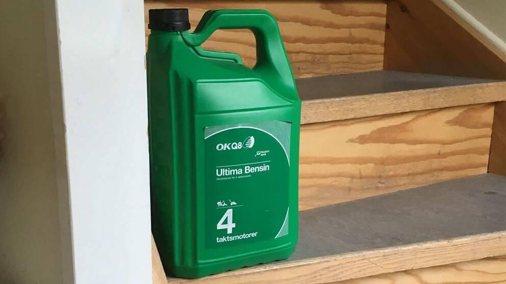 Bild på en grön plastdunk för bensin i en trapp.