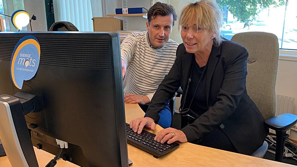 Kvinna sitter vid tangentbord bakom skärm, med man sittande bredvid.