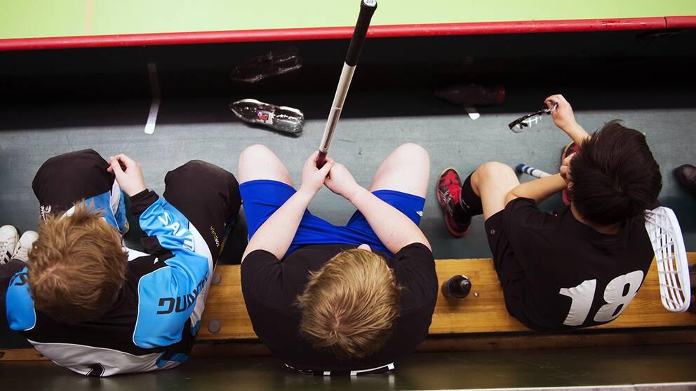 Tre barn som spelar innebandy sitter på avbytarbänken.