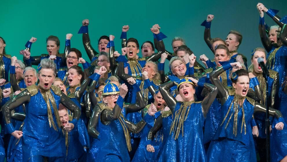 Barbershopkör klädda i blått och guld firar tillsammans på scenen.