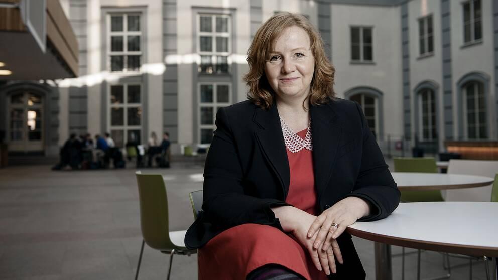 Lena Lid Falkman sitter klädd i röd klänning vid ett bord och tittar mot kameran.