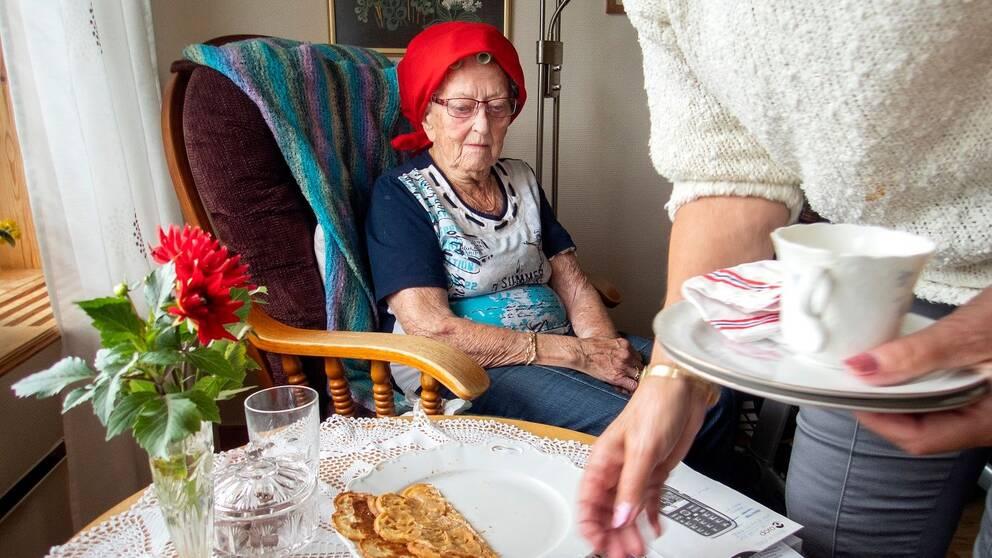 Äldre dam sitter vid ett bord och hemtjänstpersonal plockar bort disk