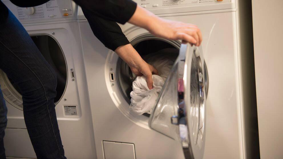 Kvinna tar ut tvätt ut en tvättmaskin.