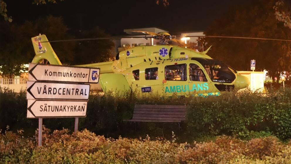 Ambulanshelikopter bakom ett buskage.