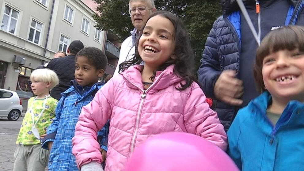 En tjej i rosa jacka skrattar så hon nästan kiknar.