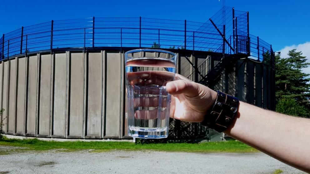 Hand som håller i ett vattenglas i förgrunden. I bakgrunden syns vattenverket i Stenungsund.
