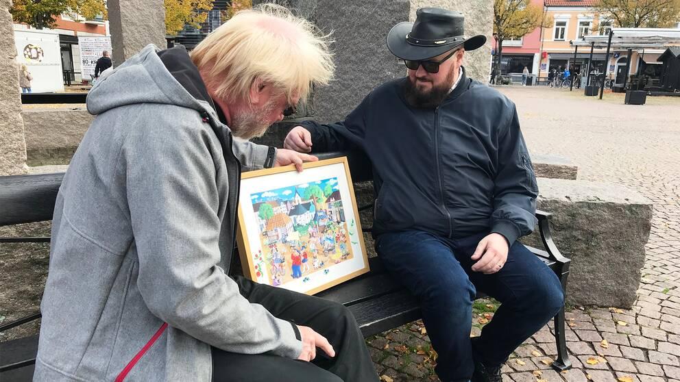 Initiativtagaren Fredrik Jansson och tidigare ordföranden Ewe Windahl tittar på ett konstverk av Rosfestivalen, målat av en lokal konstnär.