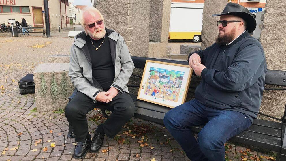 Ewe Windahl och Fredrik Jansson med konstnären Ebba-Kristina Wingårds tavla av Rosfestivalen.