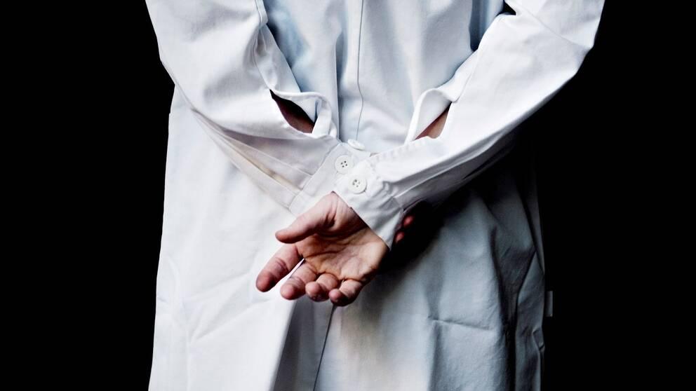 Person i läkarrock med händerna bakom ryggen