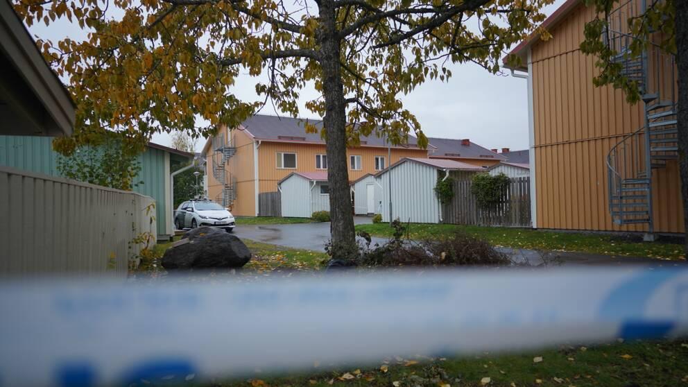 Ett polisavspärrningsband framför gula radhus. Höstlöv på marken.