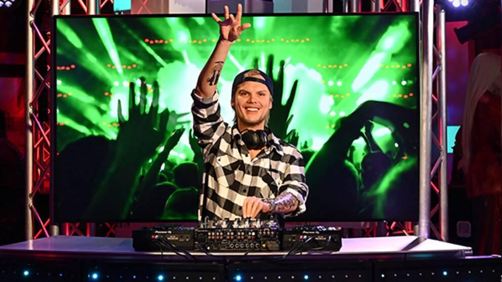 Aviciis vaxdocka. Han står vid ett DJ-bord med ena armen uppsträckt.