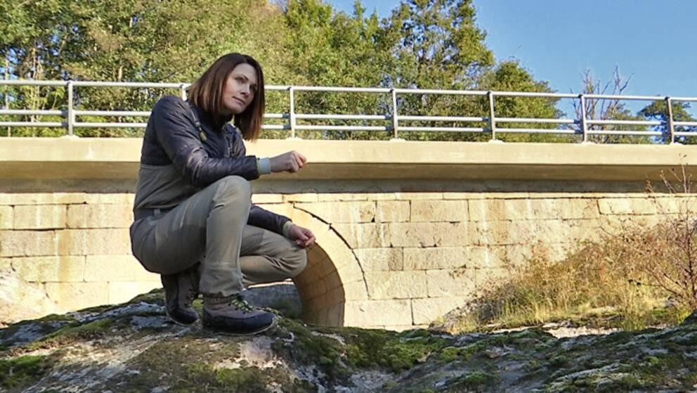 kvinna sitter på huk på en klippa