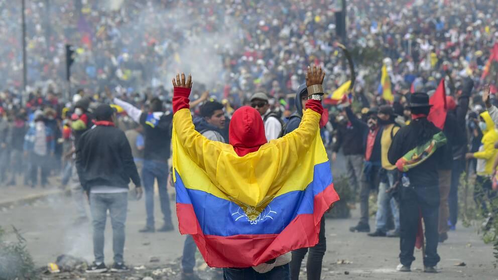 Bild på en protesterande folkmassa med en person som har Ecuadors flagga runt ryggen. Demonstrationerna sker mot president Morenos ekonomiska politik.