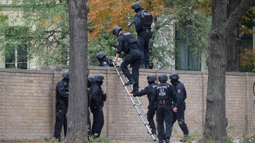 Poliser klättrar över en mur nära platsen för skjutningen i Halle.