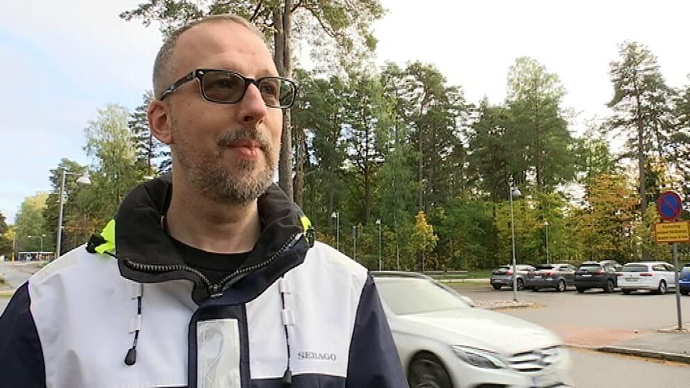 Mattias Stten står utanför en väg vid en skola. I bakgrunden kör en bil förbi.