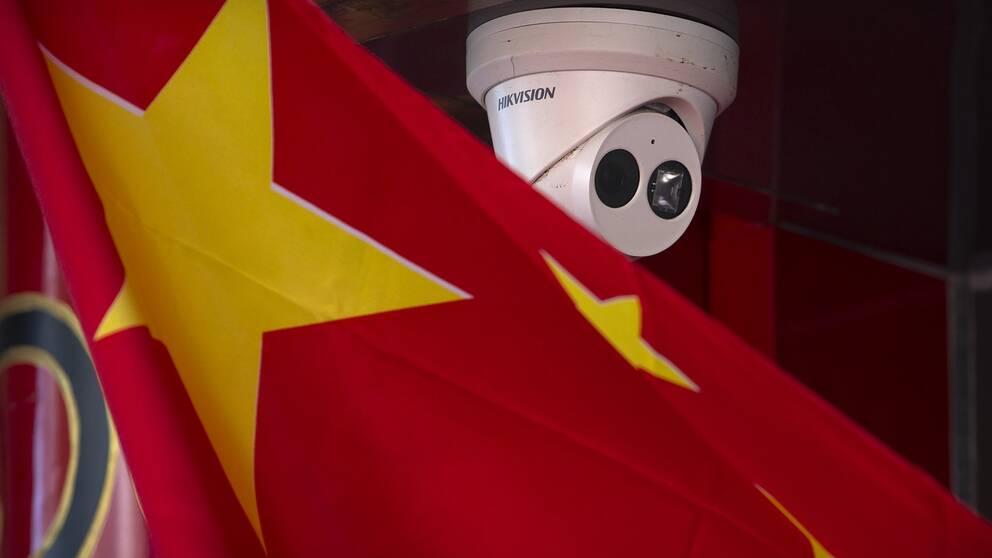 En bild på kinas flagga tillsammans med en övervakningskamera. Flera kinesiska bolag som nu svartlistats i bland annat USA skulle ha använt svensk teknik i sina övervakningskameror.