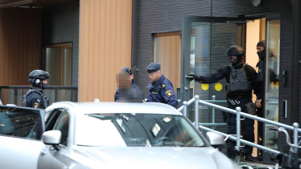 """flera polismän i uniform och maskerade poliser för ut en person som """"blurrats"""" så att den inte går att känna igen, ur ett hus"""