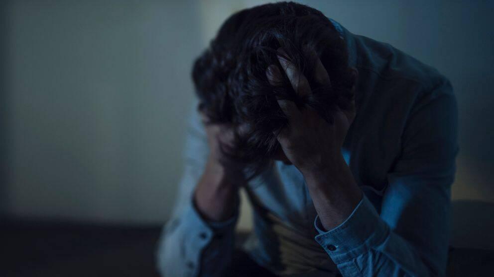 Ung man som håller händerna på huvudet med huvudet nerböjt.
