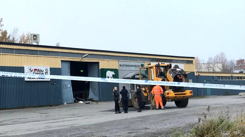 Poliser och traktor framför lagerlokal