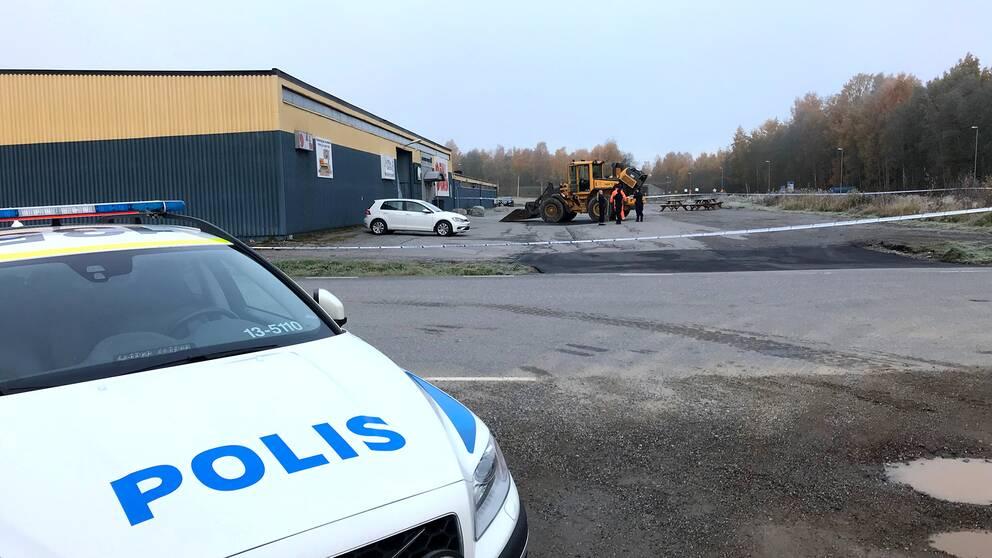 Polisbil och traktor framför lagerlokal