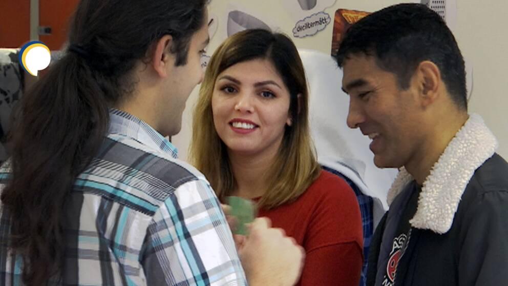 Tre personer står i grupp och pratar, en av dem tittar in i kameran